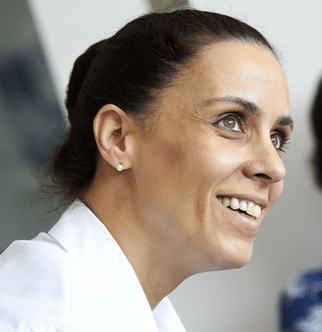 A head shot showing the profile of Inés Colmega looking up at another person out of frame.